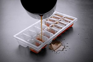 ice cube tray being filled with coffee
