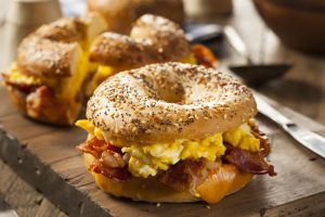 Bagel with eggs and bacon.