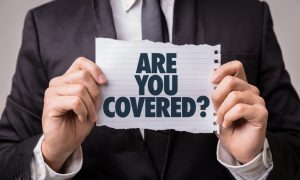 "Man holds sign saying ""are you covered?"""