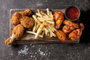 Fried chicken, french fries, and ketchup on a rectangular wooden plate