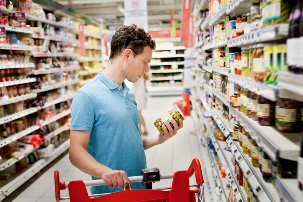 Man looking at food label while shopping