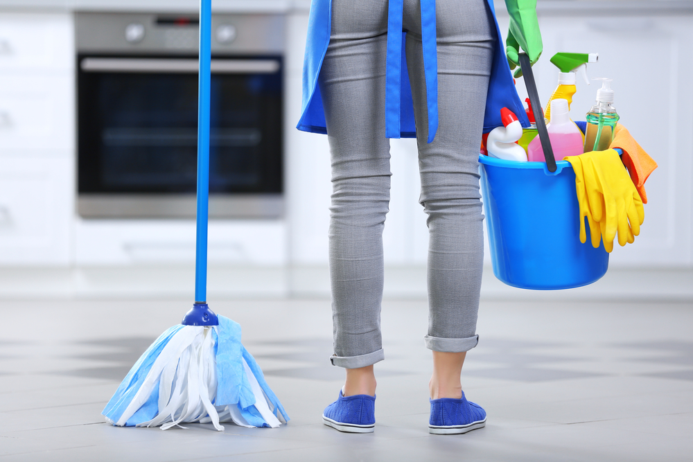 back view of woman holding mop and cleaning supplies.
