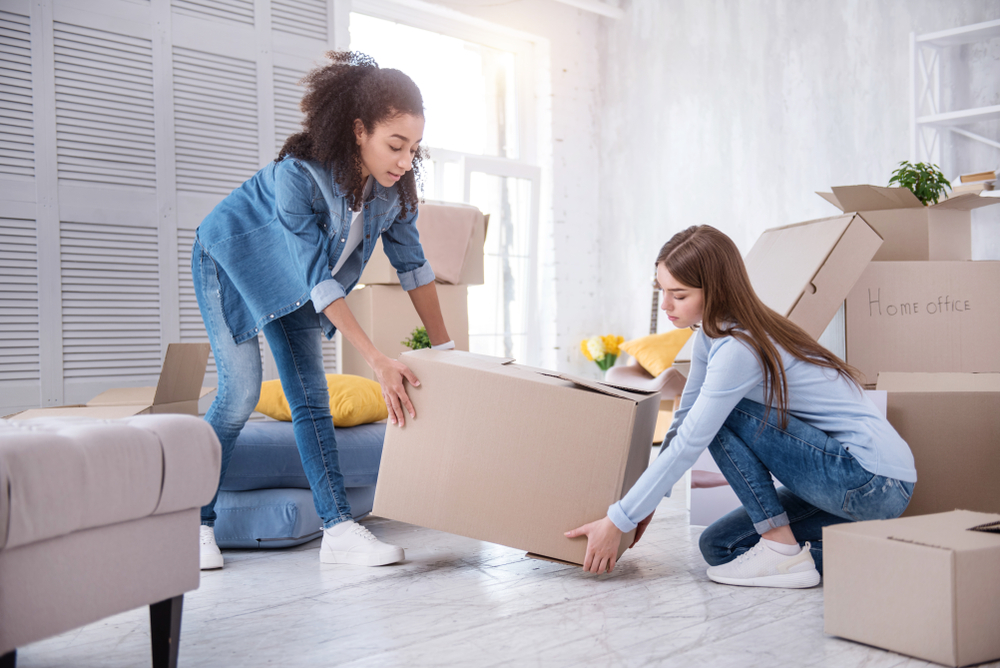 two women moving a box