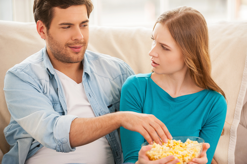woman upset about man eating her popcorn