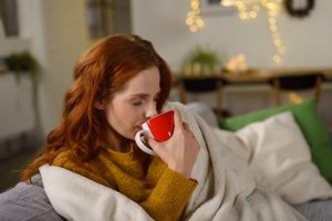 Cozy woman drinks coffee on couch with blankets.