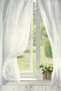Breezy open window with lace drapes.