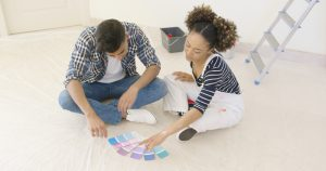 Young couple looks at paint swatches.
