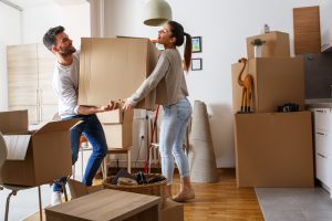 Young couple moves box into apartment.