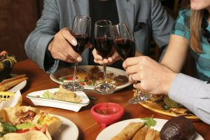Three people holding wine glasses over a table with Mexican food.