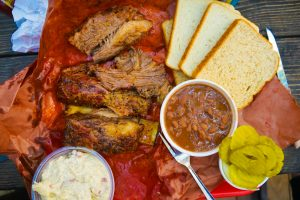 A plate of bar-b-que ribs, toast, cole slaw, baked beans, and pickles.