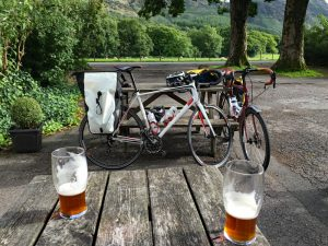 Pair of pints of beer and bikes with benches and lush green scenery