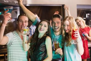 A group of people smiling and holding alcoholic drinks.