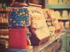 A gumball machine sitting on a counter next to candy containers.