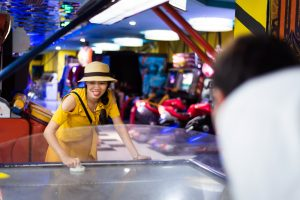 Woman in yellow dress and beige hate playing air hockey in an arcade.