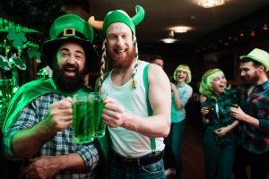 Two guys wearing St. Patrick's Day costumes and holding green beer.