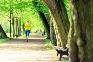 woman jogging on path in a park.