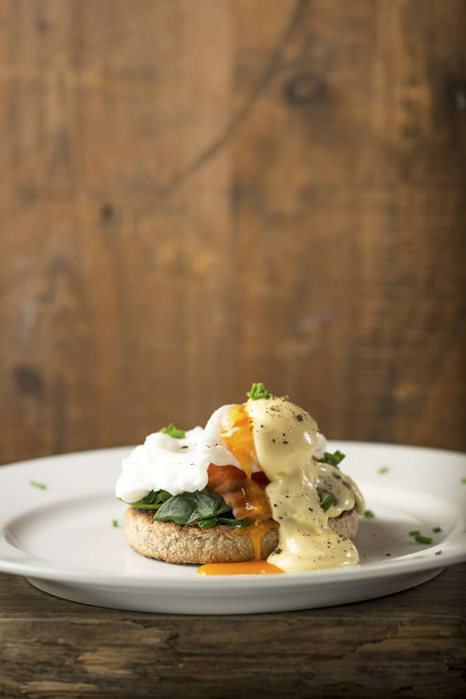 Eggs benedict with fish and spinach.