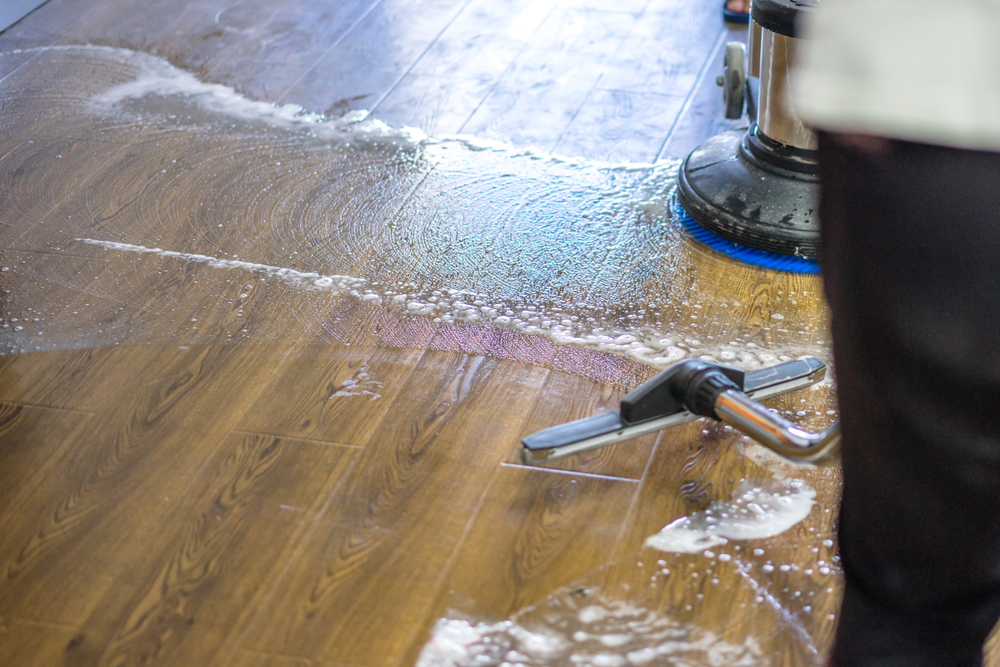 Person using a machine to clean up spill on hardwood floor.