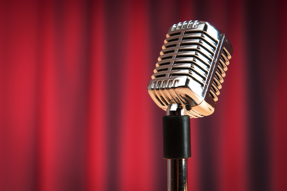 Old time microphone against red curtain