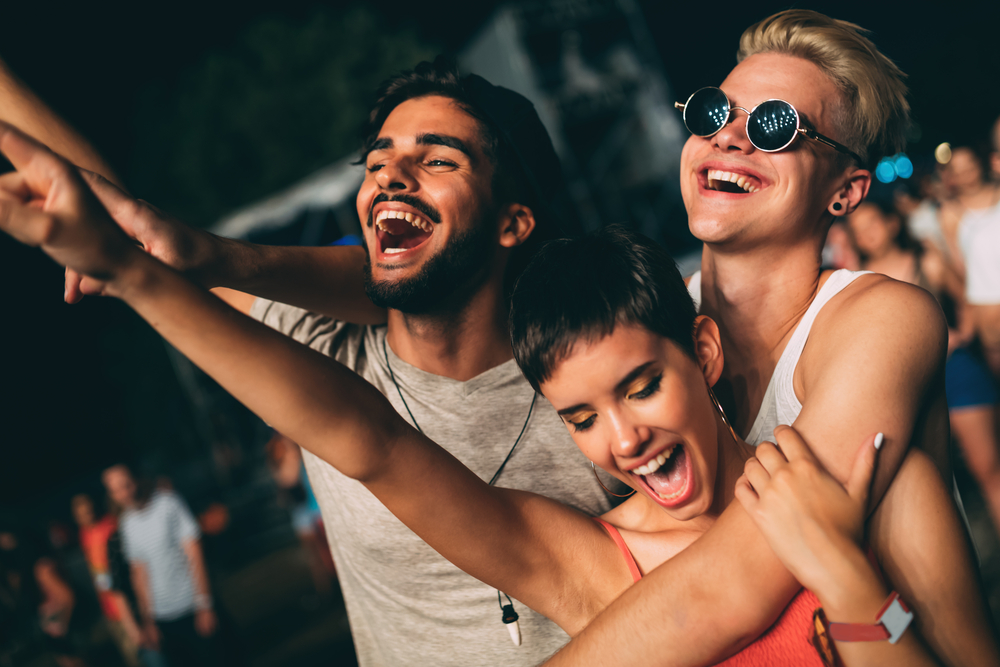 Group of friends having great time at music festival