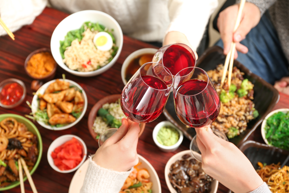 People clinking red wine glasses together over a table of Chinese food.