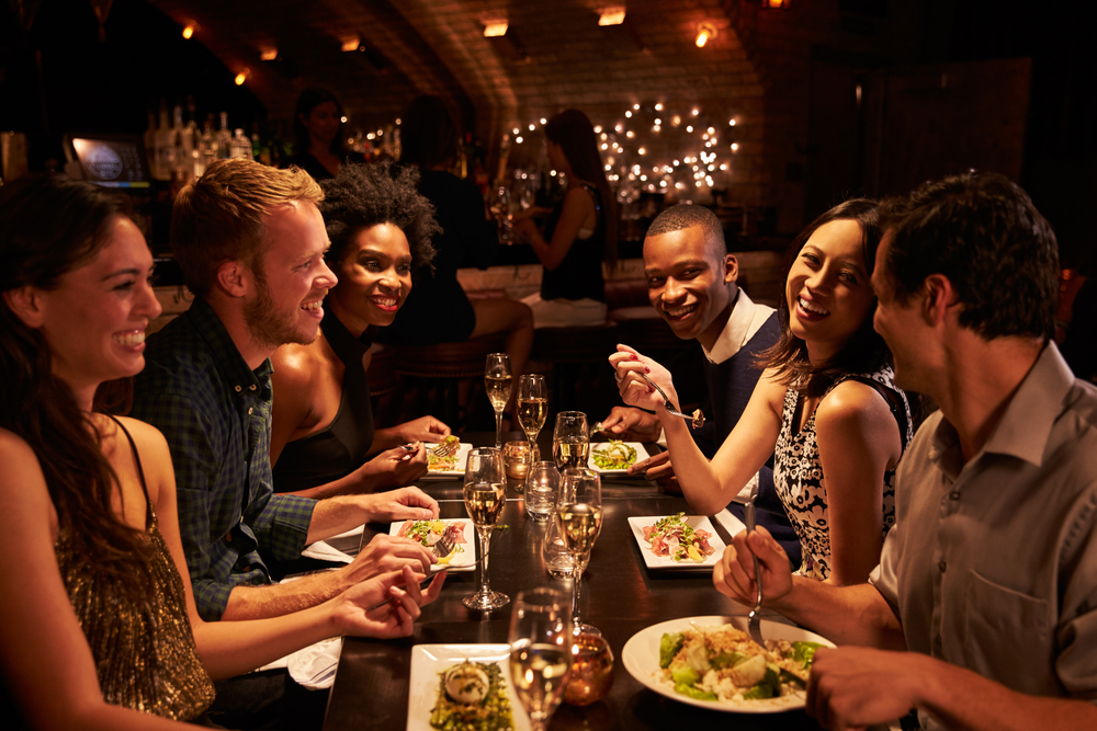 Group of ethnically diverse friends eating at a fancy Asian restaurant.