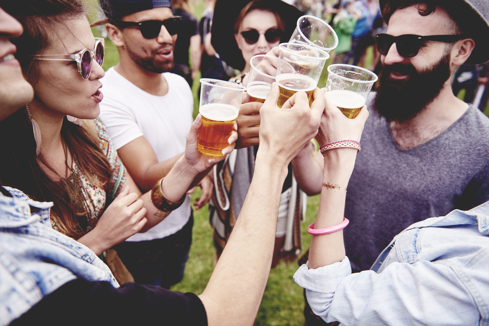 A group of friends clinking beer glasses together outside