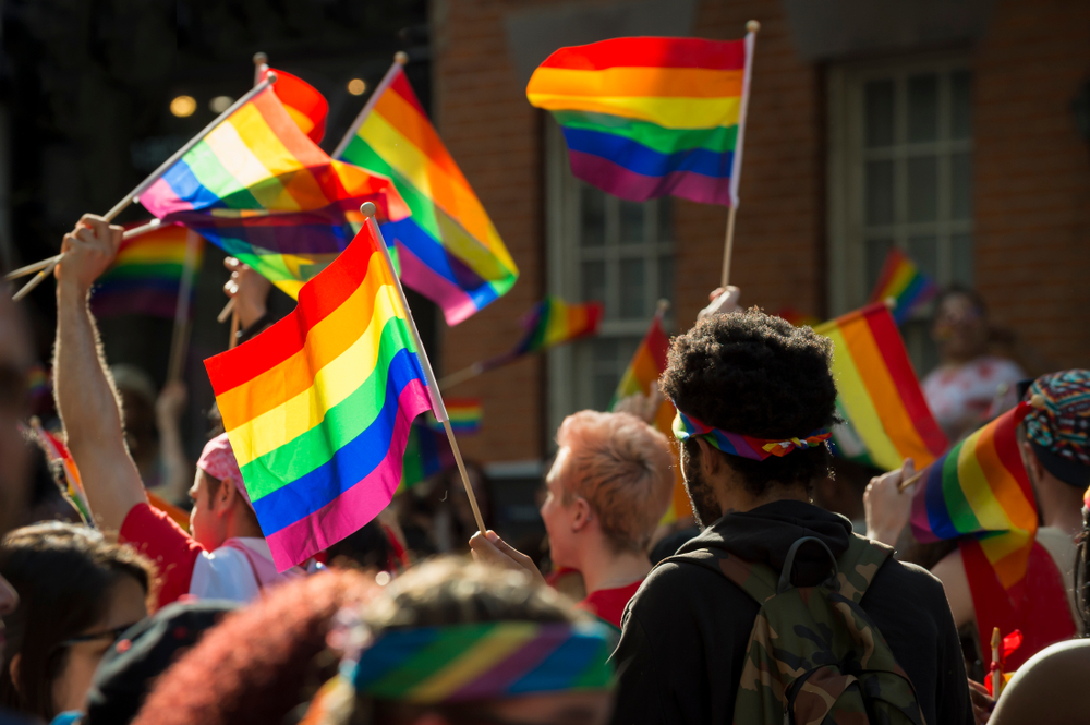A group of people holding rainbow flags at a Pride festival