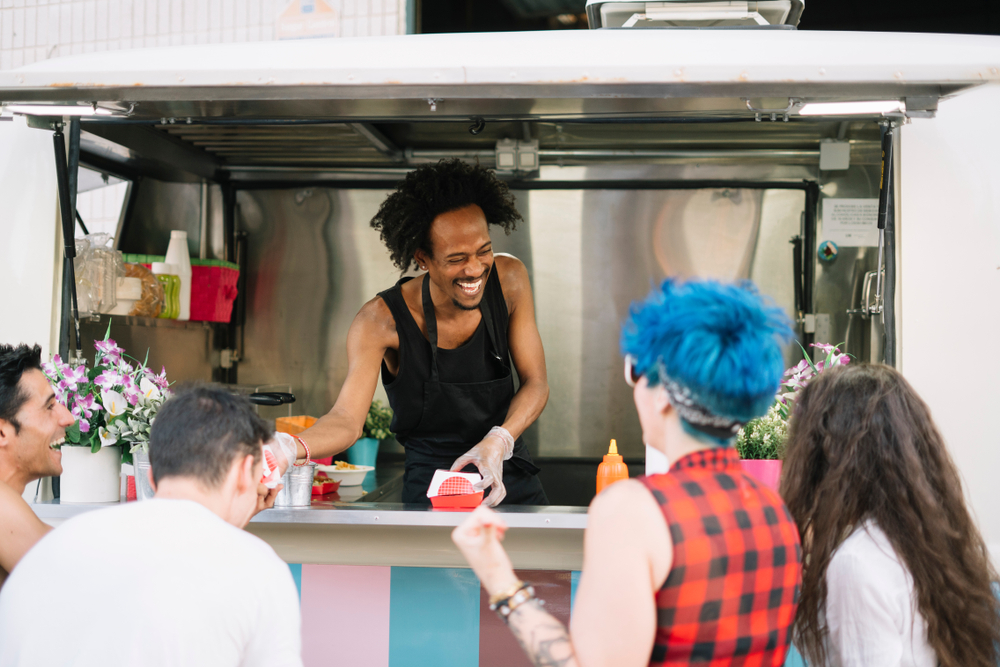 Food truck chef hands customers food.