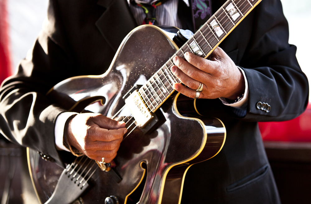 Blues musician plays his guitar.