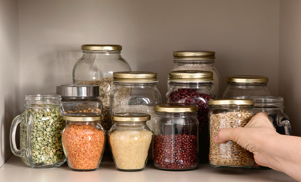 Hand arranges pantry grain jars.
