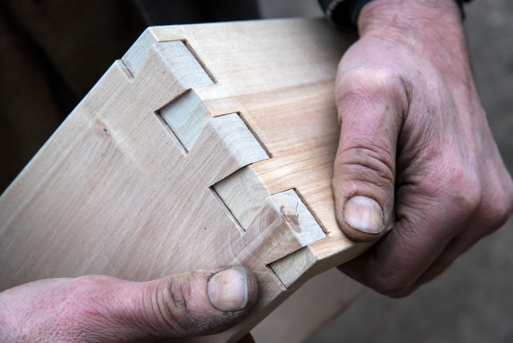 Craftsman shows off dovetail joint.
