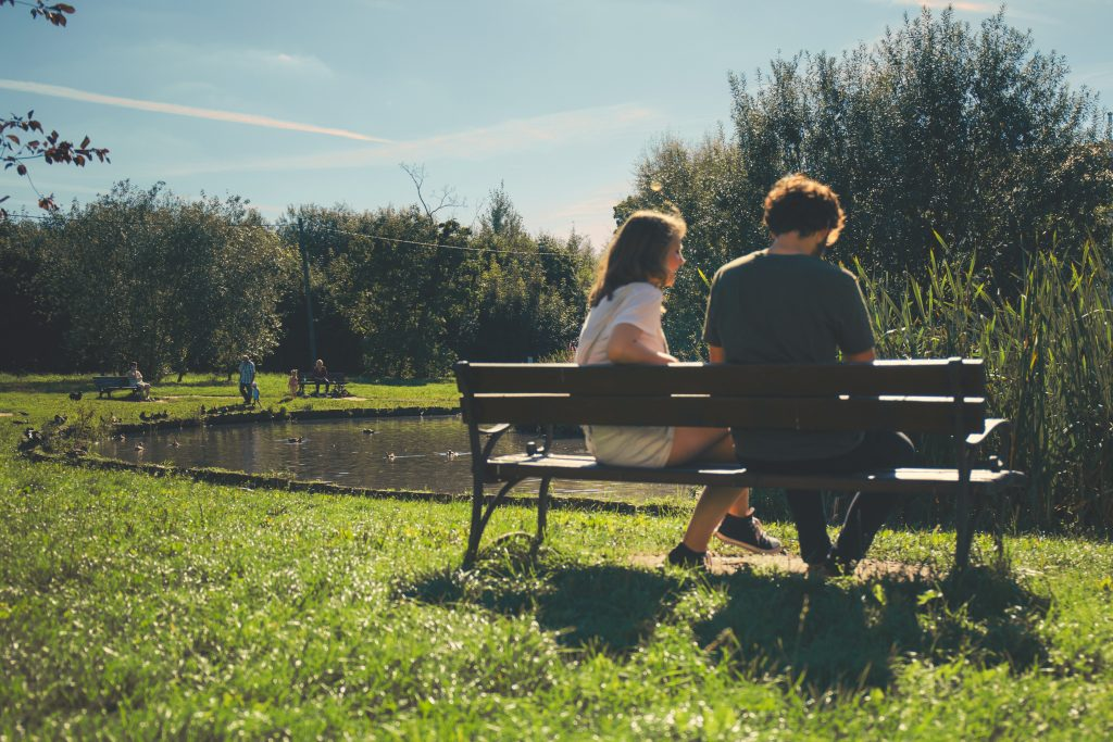 Couple sits on lakeside park bench.