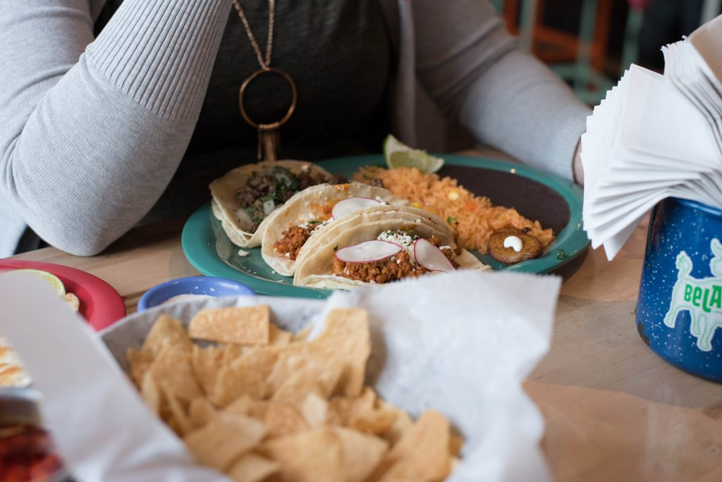 Person sitting in front of taco plate.