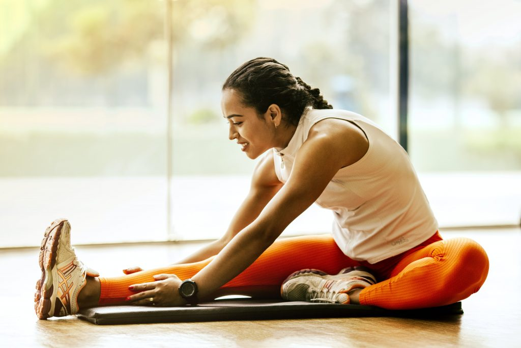 woman wearing work-out clothes stretches on apartment floor.
