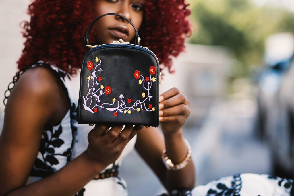 woman shows off small embroidered purse.
