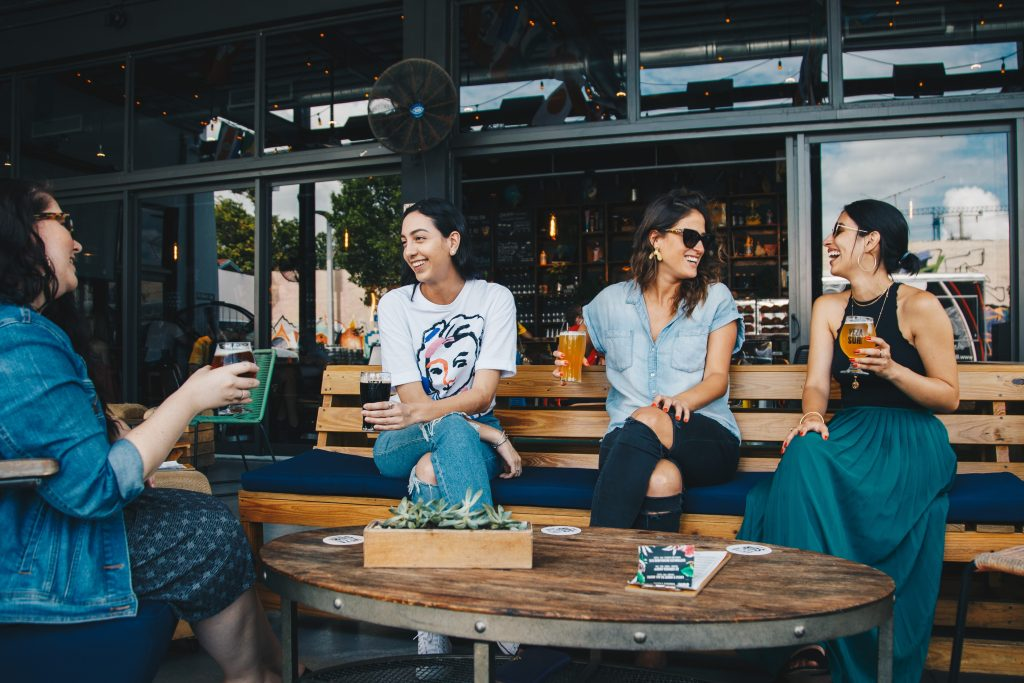 Four women sitting outside of a restaurant sharing beers.