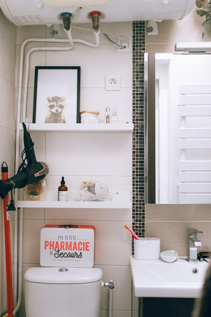 Cute bathroom shelves with bottles and framed pictures.