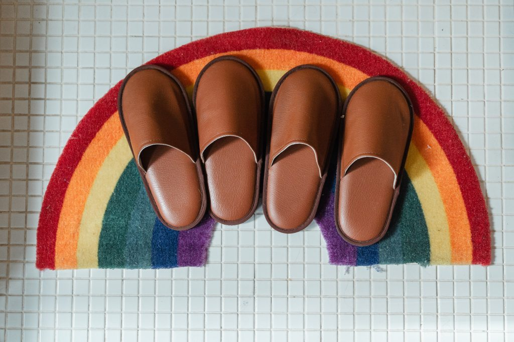Rainbow bath mat on white square tile with four leather slippers on it.