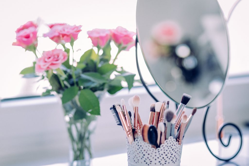 Makeup brushes in a vase next to a mirror and a vase of pink roses.