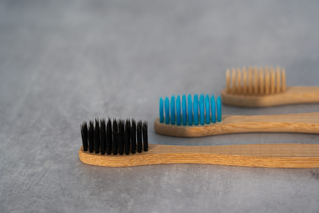 Three bamboo toothbrushes with colorful bristles.