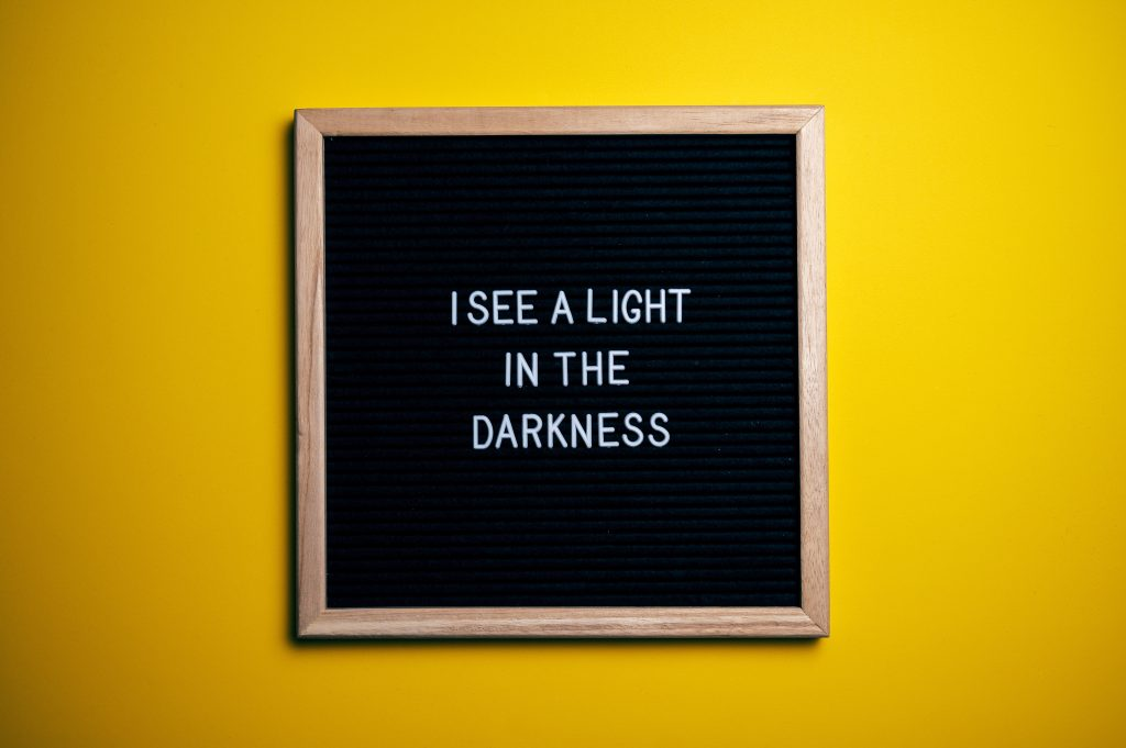 """Message board hung on yellow wall that reads """"I see a light in the darkness"""""""