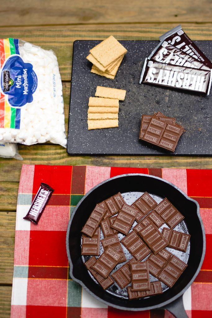 Ingredients for s'mores set up on tabletop.