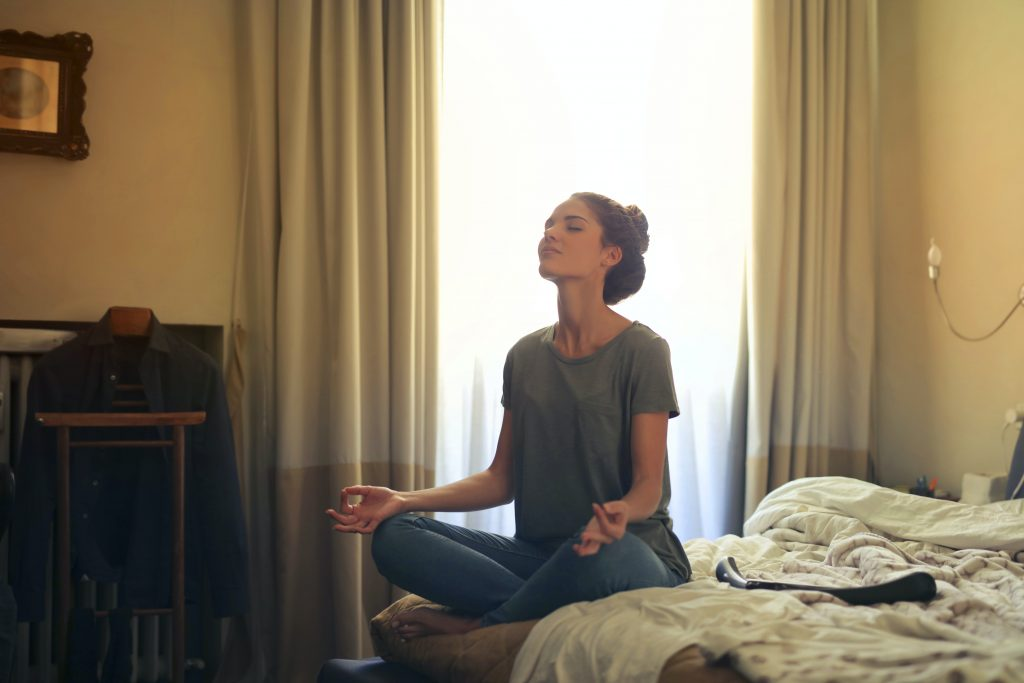 Woman meditates on bed in front of curtained window.