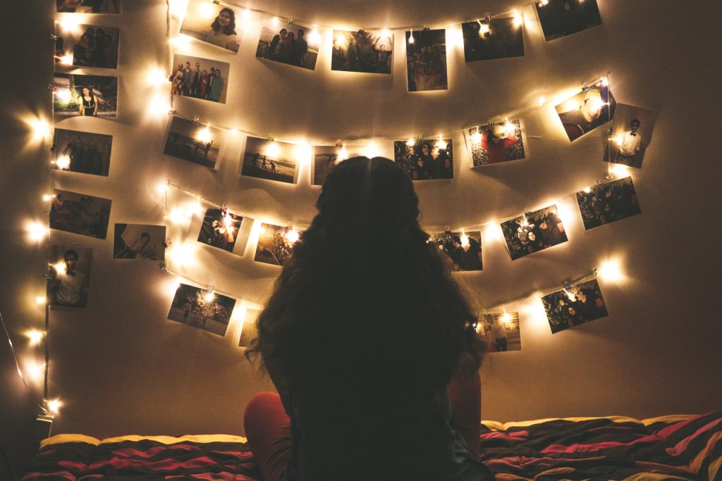 Woman sits on bed looking at photos hung on wall surrounded by Christmas lights.