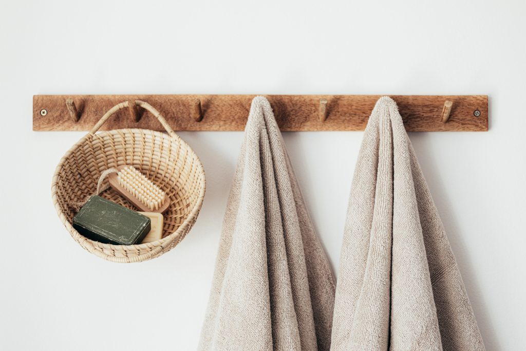 Wooden wall hanger with towels and hanging basket for bathroom products.