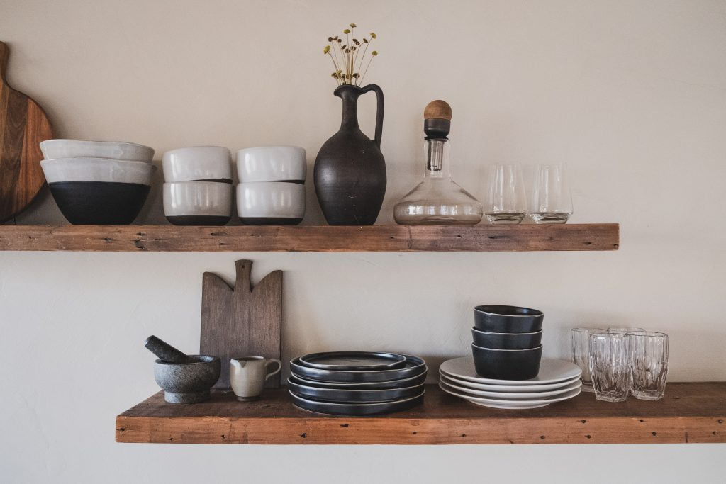 Plates, bowls, and other kitchen items on floating wooden shelves.