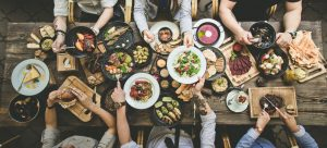 Overhead shot of long table with people sharing multiple dishes of food.