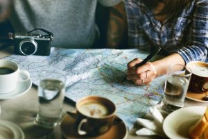 A woman writes notes on a map stretched out on the table in front of her.