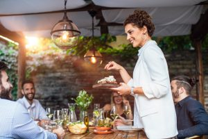 Host standing up at dinner party